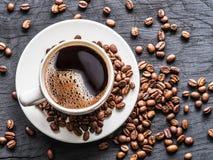 Tasse de café entourée par des grains de café Vue supérieure images stock