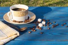 Tasse de café et beens sur une table des conseils bleus Photos stock