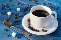Tasse de café et beens sur une table des conseils bleus Images stock