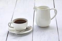 Tasse de café et crémeuse sur une table blanche Photo libre de droits