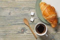 Tasse de café et croissant dans le plat photographie stock libre de droits