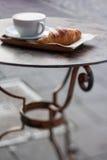 Tasse de café et de croissant sur la table en métal Photographie stock libre de droits