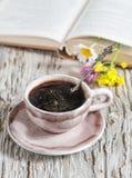 Tasse de café et de fleurs dans le livre ouvert Image libre de droits