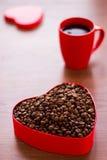 Tasse de café et de grains de café dans une boîte sous forme de coeur Photo stock