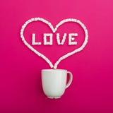 Tasse de café et de guimauves sur le fond rose Symbole de coeur et amour de citation Configuration plate Vue supérieure Images stock