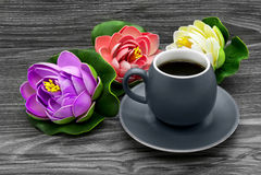 Tasse de café et de nénuphars colorés artificiels Photo stock