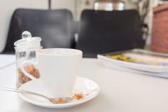 tasse de café et de sucre avec la magazine sur la table en bois blanche Images stock