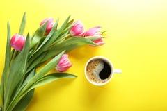 Tasse de café et de tulipes roses sur le fond jaune, vue supérieure Images libres de droits
