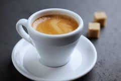 Tasse de café et de deux cubes en sucre roux sur le fond en pierre noir images libres de droits