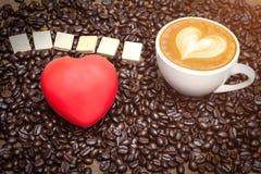 Tasse de café et grains de café, coeur rouge sur la table Image stock
