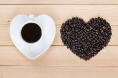 Tasse de café et grains de café en forme de coeur sur un fond en bois Image stock