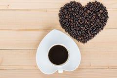 Tasse de café et grains de café en forme de coeur sur un fond en bois Photo libre de droits