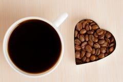 Tasse de café et grains de café sur la table en bois Image libre de droits