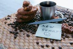 Tasse de café et grains de café sur la table en bois avec les biscuits et le bloc-notes avec le message sur l'autocollant images stock
