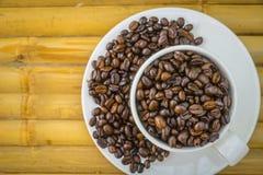 Tasse de café et grains de café sur le fond en bambou Photo stock