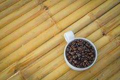 Tasse de café et grains de café sur le fond en bambou Image libre de droits