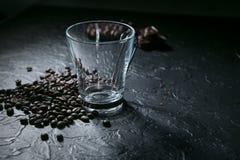 Tasse de café et grains de café vides sur le fond noir photos libres de droits