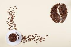 Tasse de café et grand grain de café faits de haricots dispersés image stock