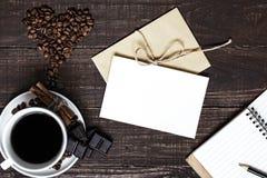 Tasse de café et haricots en forme de coeur avec la carte de voeux et le carnet Photos stock