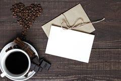 Tasse de café et haricots en forme de coeur avec la carte de voeux vierge Photos stock