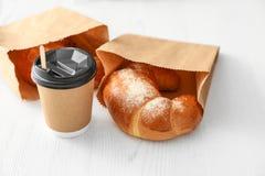 Tasse de café et de pâtisserie dans des sacs en papier photo stock