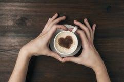 Tasse de café femelle de prise de main avec la forme de coeur sur la table en bois Image libre de droits