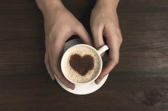 Tasse de café femelle de prise de main avec la forme de coeur sur la table en bois Photo libre de droits