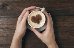 Tasse de café femelle de prise de main avec la forme de coeur sur la table en bois Photographie stock