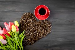 Tasse de café, grains de café et tulipes Photos libres de droits