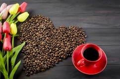 Tasse de café, grains de café et tulipes Image stock