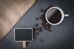 Tasse de café, grains de café et une ardoise Images libres de droits