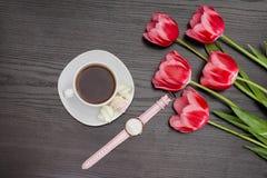Tasse de café, de guimauves, de montre et de trois tulipes roses Fond noir Photographie stock libre de droits