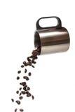 Tasse de café inoxydable versant les grains de café bruns d'isolement sur un wh Photo stock