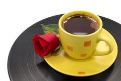 Tasse de café jaune avec la belle rose de rouge sur le disque Image libre de droits
