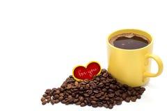 Tasse de café jaune avec les grains de café et le petit coeur rouge d'isolement Photo libre de droits