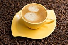Tasse de café jaune et grains de café rôtis autour Photographie stock