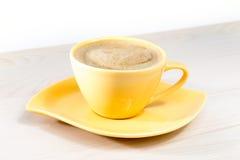Tasse de café jaune sur la table Photos libres de droits