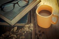 Tasse de café jaune sur la table en bois avec des livres et lunettes - modifiez la tonalité le vintage image libre de droits