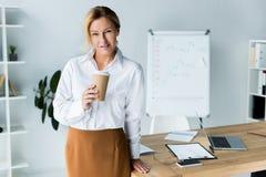 tasse de café jetable de belle participation de femme d'affaires dans le bureau et le regard image libre de droits