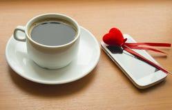 Tasse de café, le smartphone avec le coeur rouge sur une table en bois Photos libres de droits