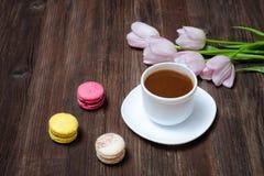 Tasse de café, de macarons et de tulipes roses sur le fond en bois À Photographie stock