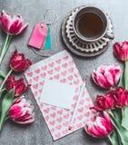 Tasse de café de matin avec la moquerie de carte de fleurs de tulipes et de papier blanc avec des coeurs, vue supérieure Photographie stock libre de droits