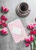Tasse de café de matin avec les tulipes roses et de carte de papier blanc avec des coeurs sur le fond de table, vue supérieure Image libre de droits