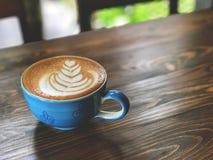 Tasse de café de matin, tasse de café d'art de latte sur le fond en bois avec la lumière de café de vintage Image libre de droits