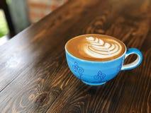 Tasse de café de matin, tasse de café d'art de latte sur le fond en bois avec la lumière de café de vintage Photos libres de droits