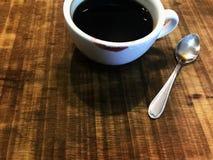 Tasse de café noir avec la marque et la cuillère d'argent rouges de rouge à lèvres Photo stock