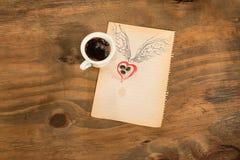 Tasse de café noir avec le coeur de grains de café avec des ailes dessinées au crayon Photographie stock libre de droits