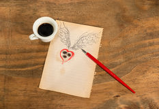 Tasse de café noir avec le coeur de grains de café avec des ailes dessinées au crayon et la rose de rouge Photo libre de droits