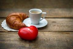 Tasse de café noir avec le croissant et la bougie rouge de coeur Photo libre de droits