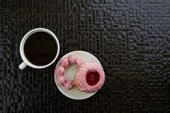 Tasse de café noir avec les butées toriques roses Photos libres de droits